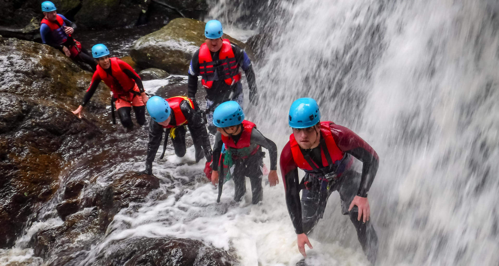 Group enjoy walking under waterfall on a multi activity holiday