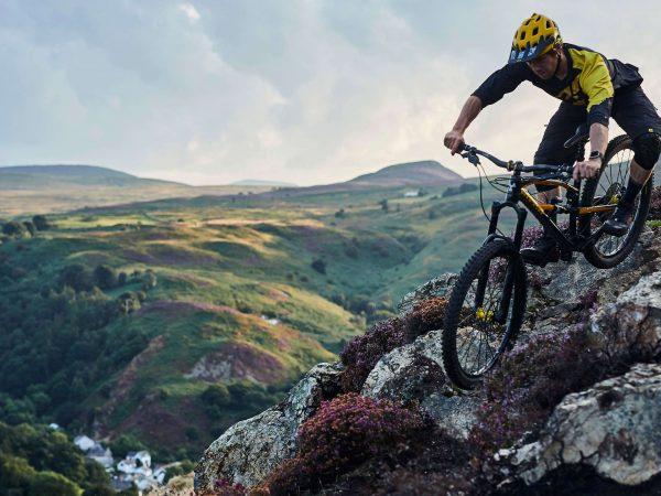 Mountain biker riding rocky trail in Wales on short MTB break