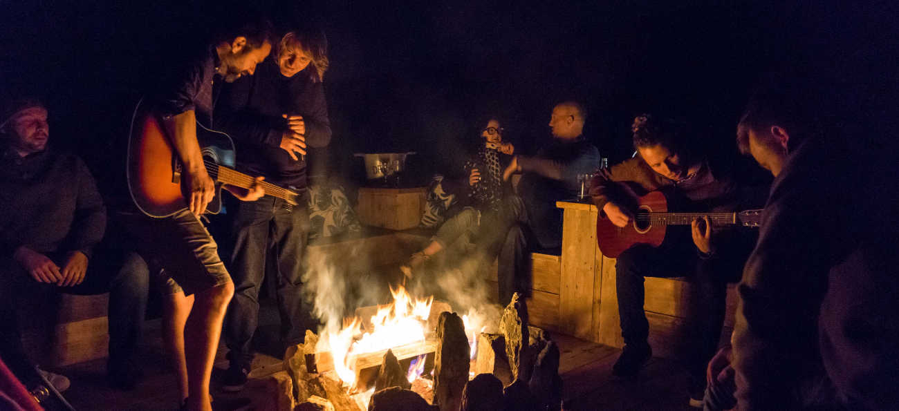 mountain bikers party around camp fire