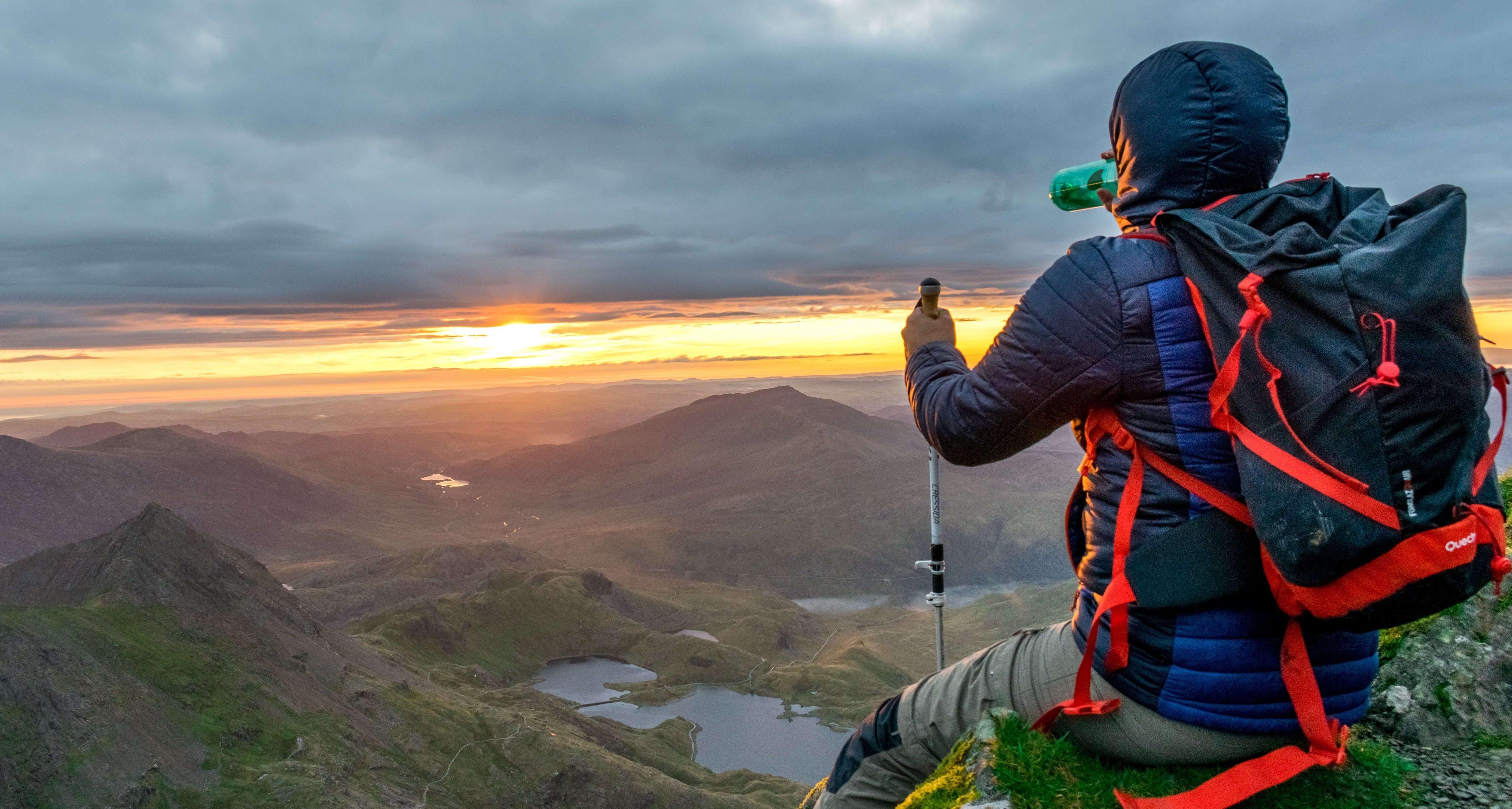 Hiker watching sunset over Snowdonia